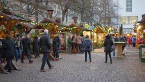 Bezige Kerstmismarkt met een het lopen menigte op achtergrond van verlichte voedselboxen en houten winkels stock videobeelden