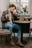 Bezige mens die hebbend een koffie en gelijktijdig houdend een hond werken royalty-vrije stock afbeelding