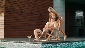 Bezige mensenzitting met mobiele dichtbijgelegen pool bij privé villa stock video