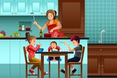 Bezige moeder in de keuken met haar jonge geitjes Stock Afbeeldingen