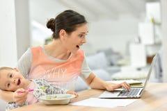 Bezige moeder die aan laptop werken en haar baby voeden Stock Afbeelding