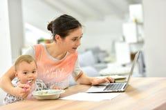 Bezige moeder die aan laptop werken en haar baby voeden Stock Afbeeldingen