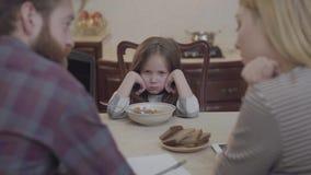 Bezige moeder en vader die aan de keuken bij de lijst met hun ruggen aan camera werken Weinig ongelukkige meisjeszitting binnen stock footage