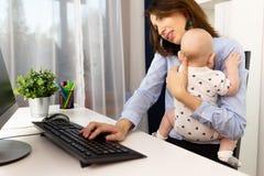 Bezige onderneemsters die op een kantoor met een baby aan haar handen werken royalty-vrije stock foto's
