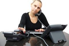 Bezige secretaresse in bureau met twee telefoons stock foto