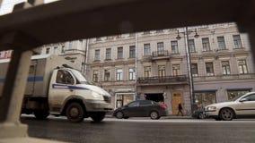 Bezige straat met gebouwenvoorgevels, lopende mensen, grote weg met opstopping stock video
