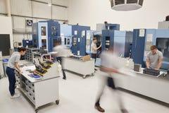 Bezige Techniekworkshop met Arbeiders die CNC Machines met behulp van stock foto's