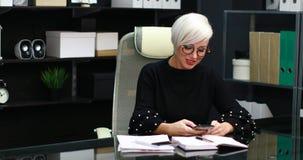 Bezige vrouw die op mobiele en landline zitting bij lijst in bureau spreken stock video