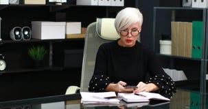 Bezige vrouw die op mobiele en landline zitting bij lijst in bureau spreken stock videobeelden