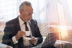 Bezige werkende heer het drinken koffie bij laptop royalty-vrije stock fotografie