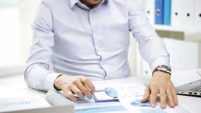 Bezige zakenman met laptop en documenten in bureau stock video