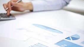 Bezige zakenman met laptop en documenten in bureau stock videobeelden