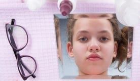 bezinning in de spiegel, een close-up van het meisje, om glazen met contactlenzen te vervangen royalty-vrije stock afbeeldingen