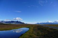Bezinning in een meer naast de ringsweg op een glorierijke zonnige dag, IJsland stock foto's