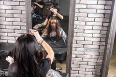 Bezinning in grote spiegel van aantrekkelijke donkerbruine vrouwelijke stilist stock fotografie