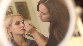 Bezinning in spiegel van een een make-upkunstenaar en model stock videobeelden