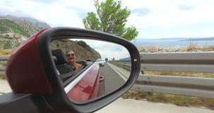Bezinning van aantrekkelijke blondevrouw in zijspiegel van convertibel stock video