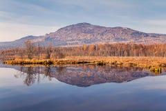 Bezinning van berg in blauw water royalty-vrije stock afbeeldingen