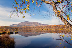 Bezinning van berg en hemel in blauw water stock foto