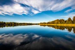 Bezinning van blauwe hemel en wolken op een rivier stock afbeeldingen