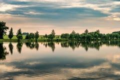 Bezinning van bomen in een meerwater op een stille de zomeravond royalty-vrije stock foto's