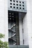 Bezinning van brandtrap in het glas van een modern gebouw met grijze cementmuren stock afbeeldingen