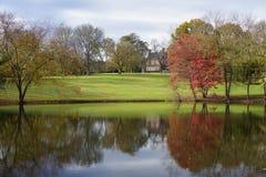 Bezinning van dalingsgebladerte, groen gras en een huis in de kalme wateren van een vijver in Noord-Carolina stock afbeeldingen