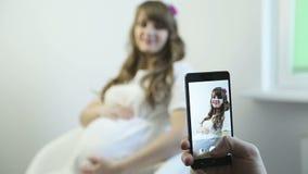 Bezinning van de aanstaande moeder in witte kleding op het telefoonscherm stock footage