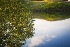 Bezinning van de hemel op de waterspiegel van het meer stock foto