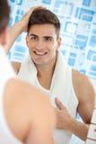 Bezinning van de jonge mens in spiegel Stock Fotografie