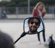 Bezinning van de mens met glazen en baard die in een motorspiegel glimlachen stock afbeelding