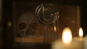 Bezinning van de schedel en de kaarsen in de slinger van een oude klok stock video
