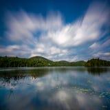 Bezinning van de wolken die over een meer gaan Royalty-vrije Stock Afbeeldingen