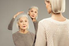 Bezinning van een ernstige oude vrouw in de spiegel royalty-vrije stock afbeeldingen
