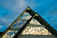 Bezinning van een hemel in een vorm van het driehoeksglas op een gebouw bij Afgetapt Royalty-vrije Stock Foto