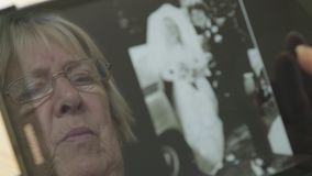 Bezinning van een hogere vrouw die oude foto's op een tabletcomputer bekijken stock videobeelden