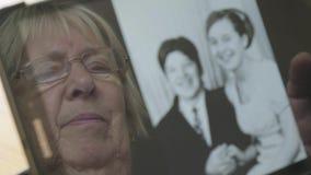 Bezinning van een hogere vrouw die oude foto's op een tabletcomputer bekijken stock video