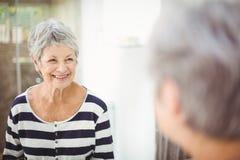 Bezinning van gelukkige hogere vrouw op spiegel royalty-vrije stock afbeelding