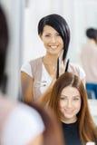 Bezinning van herenkapper die haarstijl voor vrouw doen Stock Afbeeldingen