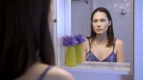 Bezinning van ongelukkige mooie vrouw in spiegel stock video