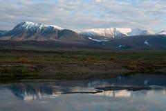 Bezinning van snow-covered bergen in een rustige rivier stock fotografie