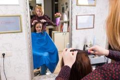 Bezinning van Stilist die Haar van Cliënt kammen stock fotografie