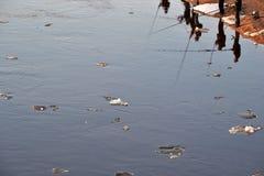 Bezinning van vissers in vuil rivierwater met zwemmend smeltend ijs in de lentetijd stock foto's
