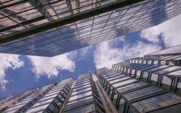 Bezinning van wolken in glasmuren van wolkenkrabbers in de grote stad en de blauwe hemel met witte wolken royalty-vrije stock fotografie