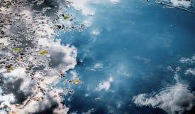 Bezinning van wolken in kalm water stock afbeelding
