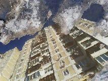 Bezinning in vulklei: op de waterspiegel een woon geel huis op grote hoogte, die de hogere vloeren in de blauwe hemel, s verlaten Stock Afbeelding