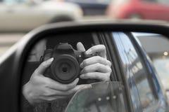 Bezinning in zijaanzichtspiegel van iemand met camera royalty-vrije stock foto's