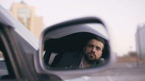 Bezinning in zijspiegel van de jonge zitting van de privé-detectivemens binnen auto en het fotograferen met dslrcamera stock footage