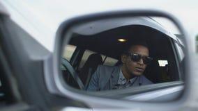 Bezinning in zijspiegel van de zitting van de politiemens binnen auto en het fotograferen met dslrcamera stock footage