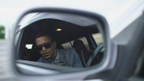 Bezinning in zijspiegel van Paparazzi-mensenzitting binnen auto en het fotograferen met dslrcamera stock video